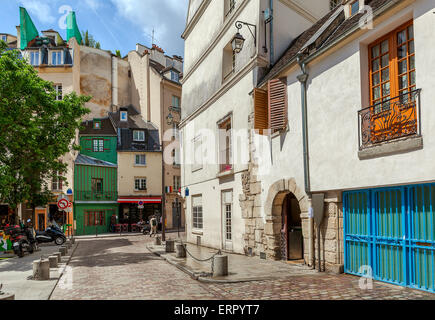 View on narrow street among typical parisian buildings in Paris, France. - Stock Photo