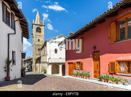 Narrow cobblestone street among typical houses and old abandoned church on background in small italian town in Piedmont, - Stock Photo