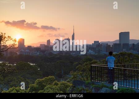 Man taking photo of city skyline from Fukuoka Castle ruins at sunset, Fukuoka, Kyushu, Japan - Stock Photo