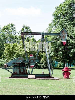 Old oil pump in the exhibition field of urban park. - Stock Photo