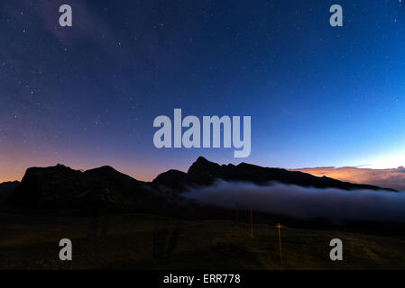 evening at the Rolle pass with fog on the mountains and blue sky with stars background, Trentino - Italy - Stock Photo