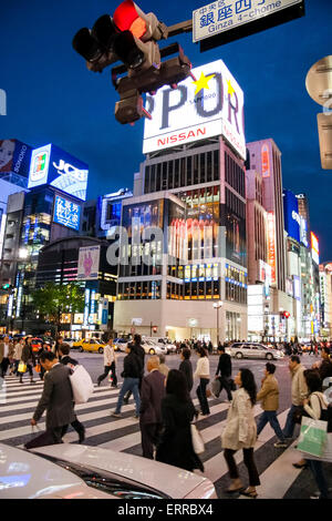 Japan, Tokyo, Ginza. 4-chome Intersection, people crossing street, with illuminated signs and stores in background, - Stock Photo