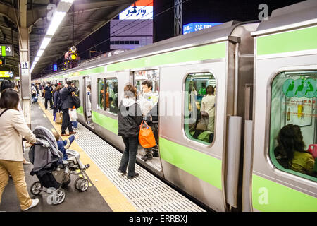 Japan, Toyko. Train at platform, people getting on and off, mother pushing pushchair towards open carriage door, - Stock Photo
