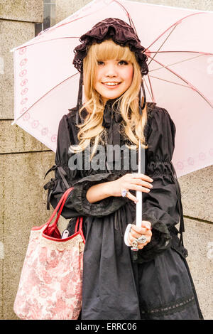 Japanese cosplay, Harajuku, Toyko. Woman dressed up in 'Sweet Lolita' Classic Lolita style holding pink umbrella - Stock Photo