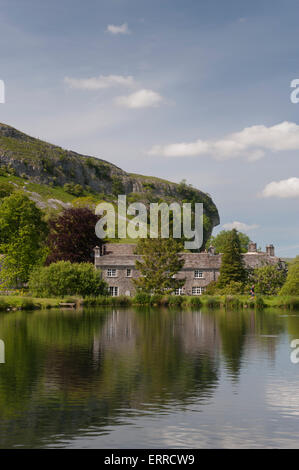 Summer sunlight & quaint stone cottages stand on the banks of a scenic fishing lake, Kilnsey Crag beyond - Kilnsey - Stock Photo