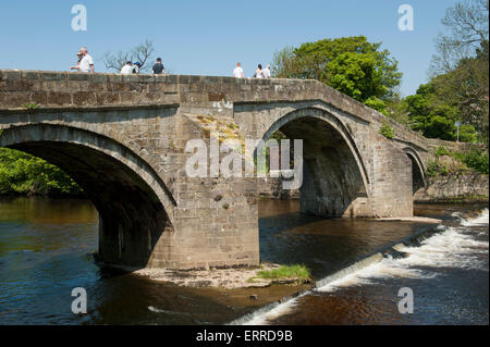 People crossing scenic River Wharfe on old stone packhorse bridge over flowing water & small weir - Old Bridge, - Stock Photo