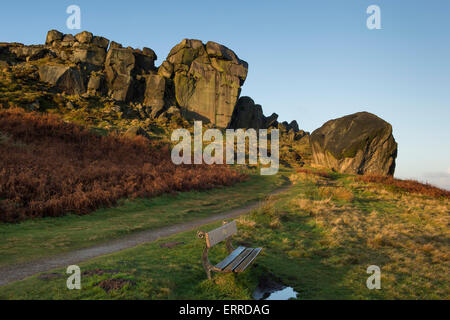 Scenic rural landscape of blue sky & early winter morning sunlight on a rocky outcrop - Cow and Calf Rocks, Ilkley - Stock Photo