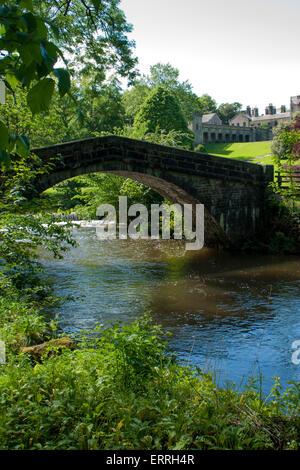 Stone bridge over the River Manifold at Ilam Hall, Ilam, Staffordshire Peak District, UK. Ilam Hall in the background. - Stock Photo
