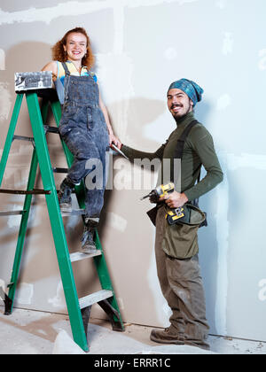 Portrait of a smiling young couple renovating, patching up drywall - Stock Photo
