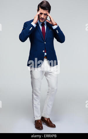 Full length portrait of a young businessman with headache over gray background - Stock Photo
