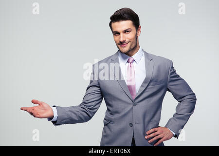 Businessman with arm out in a welcoming gesture over gray background - Stock Photo