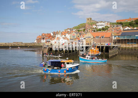 boats in Whitby Harbour with the Old Town and Church of Saint Mary, Yorkshire, England - Stock Photo