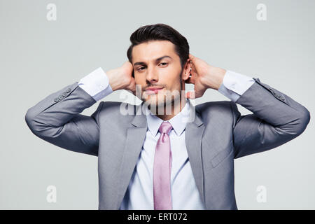 Portrait of a businessman covering his ears over gray background and looking at camera - Stock Photo