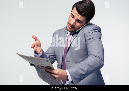 Businessman talking on the phone and reading newspaper over gray background - Stock Photo