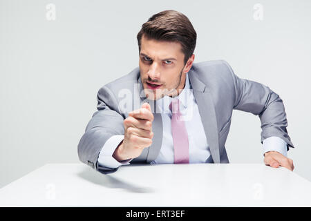 Angry businessman sitting at the table over gray background. Looking at camera - Stock Photo
