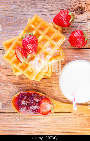homemade waffles with strawberry jam and glass with milk on wooden background - Stock Photo