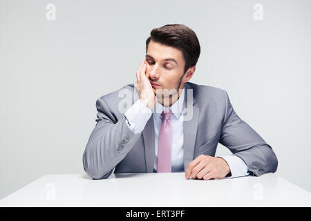Tired businessman sitting at the table over gray background - Stock Photo