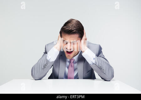 Dissapointed businessman sitting at the table and covering his ears over gray background - Stock Photo