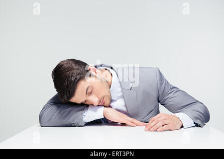 Businessman sleeping on the table over gray background - Stock Photo