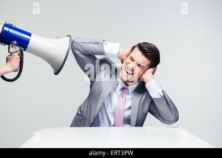 Businessman sitting at the table and covering his ears from megaphone over gray background - Stock Photo