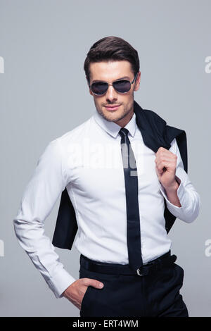 Fashion businessman with jacket on shoulder and sunglasses standing over gray background and looking at camera - Stock Photo