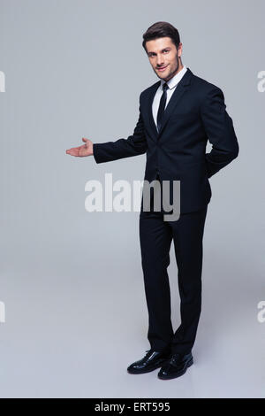 Full length portrait of a businessman with arm out in a welcoming gesture over gray background - Stock Photo