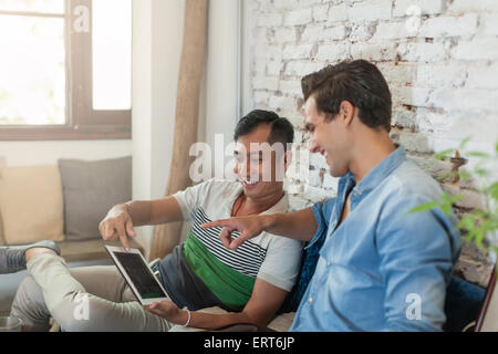 Two Men Using Tablet Computer Internet at Cafe - Stock Photo
