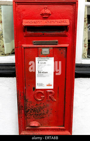 Weathered iconic red letterbox attached on the facade of the Old Post Office in Dorchester-on-Thames, Oxfordshire, - Stock Photo