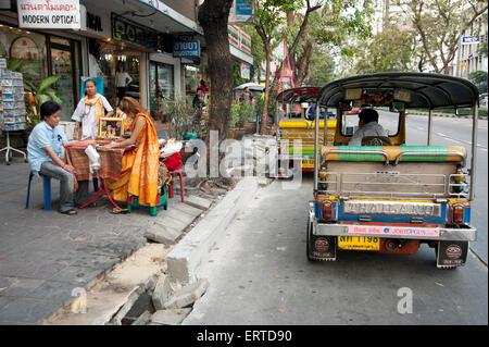 Fortune teller on the streets of Bangkok with a tuk tuk taxi waiting on the roadside Bangkok Thailand - Stock Photo