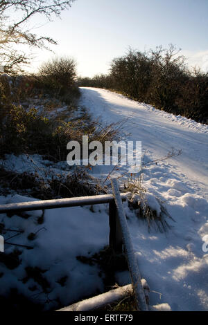 Footprints on a snow covered road at sunset, Glen Whilly, New Luce, Dumfries and Galloway, Scotland - Stock Photo