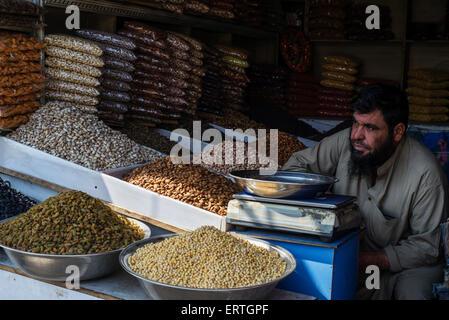 Afghan man sells nuts and seeds in street market in Third Macrorayan, neighborhood built-up by Soviet multistorey - Stock Photo