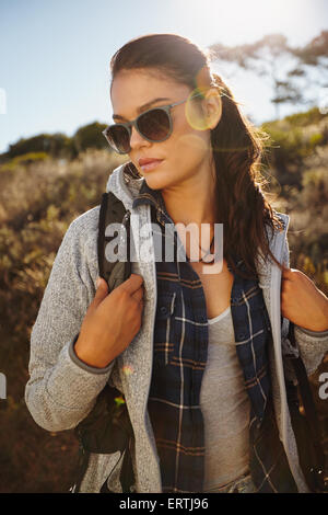 Portrait of an attractive young female hiker in nature. Caucasian young woman wearing sunglasses and carrying a - Stock Photo