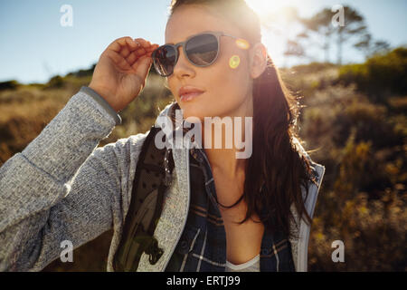 Portrait beautiful young woman hiking on a summer day. Caucasian female wearing sunglasses looking away, outdoors - Stock Photo