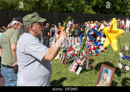 A Vietnam veteran snaps a picture of wreaths while other visitors view names on the Vietnam Veterans Memorial in - Stock Photo