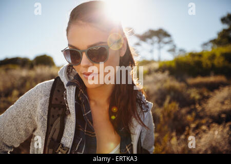 Outdoor shot of young woman hiking in a sunlit nature reserve. Pretty young female hiker wearing sunglasses looking - Stock Photo