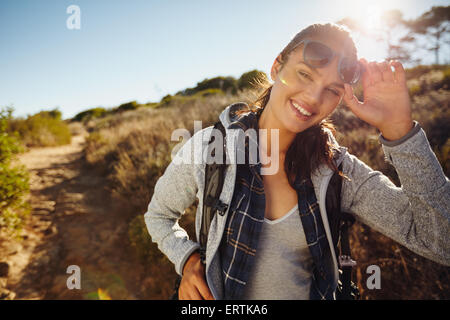 Portrait of a happy young hiker woman in nature. Young caucasian woman wearing sunglasses looking at camera with - Stock Photo