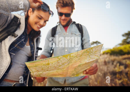 Young couple reading map on country walk. Caucasian hiker couple on hike looking directions on map in hand. Focus - Stock Photo
