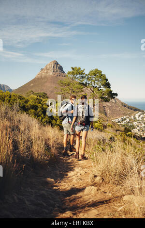 Portrait of couple of hikers walking through pathway on mountain. Man and woman enjoying summer vacation in countryside - Stock Photo