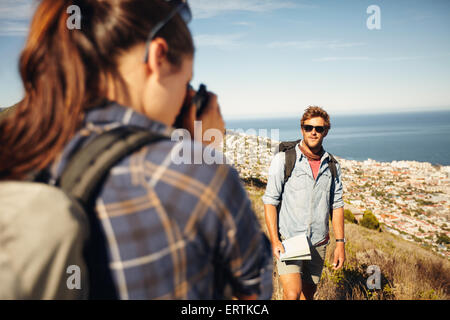 Young man posing in nature, with woman talking his pictures in countryside on a summer day while hiking. Young woman - Stock Photo