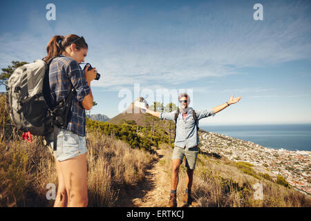 Outdoor shot of young woman photographing her boyfriend in countryside while hiking. Hiker couple enjoying during - Stock Photo