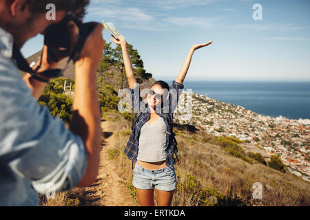 Happy young woman posing with her arms raised to her boyfriend taking her photos with digital camera. Summer vacation - Stock Photo