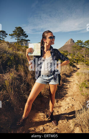 Portrait of beautiful young woman posing with a map outdoors. Caucasian woman hiking in a summer day, looking away - Stock Photo