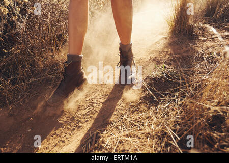 Young woman's feet as she hikes on a mountain trail with puff of dust. Woman hiking on dirt path in countryside. - Stock Photo
