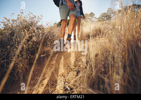 Low angle view of young couple walking on country trail path. Couple hiking on mountain coming downhill. Cropped - Stock Photo