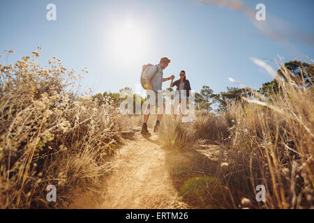 Outdoor shot of young couple on hiking trip, walking on dirt trail in mountains holding hands. Young man and woman - Stock Photo