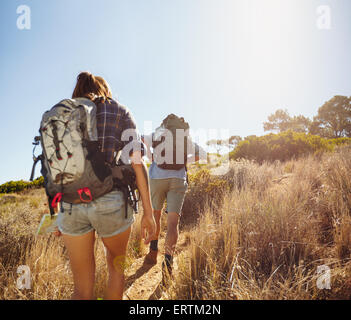 Rear view image of two young people carrying backpacks walking through mountain trial on summer day. Man and woman - Stock Photo