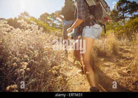 Cropped image of man and woman walking on country trail path. Young couple hiking on mountain on sunny day. - Stock Photo
