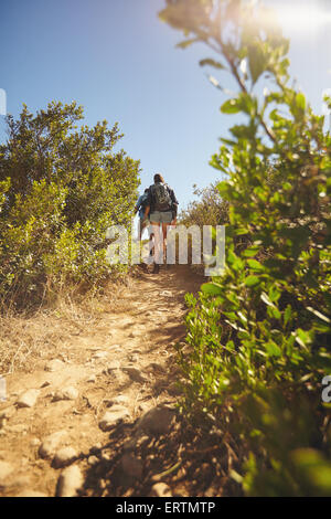 Image of people walking through mountain trail. Rear view shot of couple hiking on dirt path through grass and plants - Stock Photo