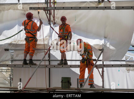 Construction workers erecting scaffolding and encasing it in plastic tent for protection from weather, UK - Stock Photo