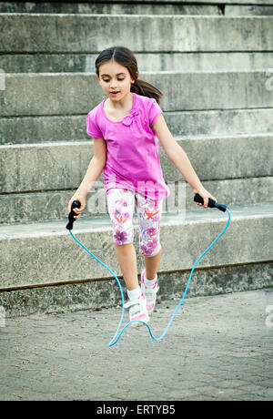 Happy attractive little girl in a trendy pink outfit skipping outdoors - Stock Photo